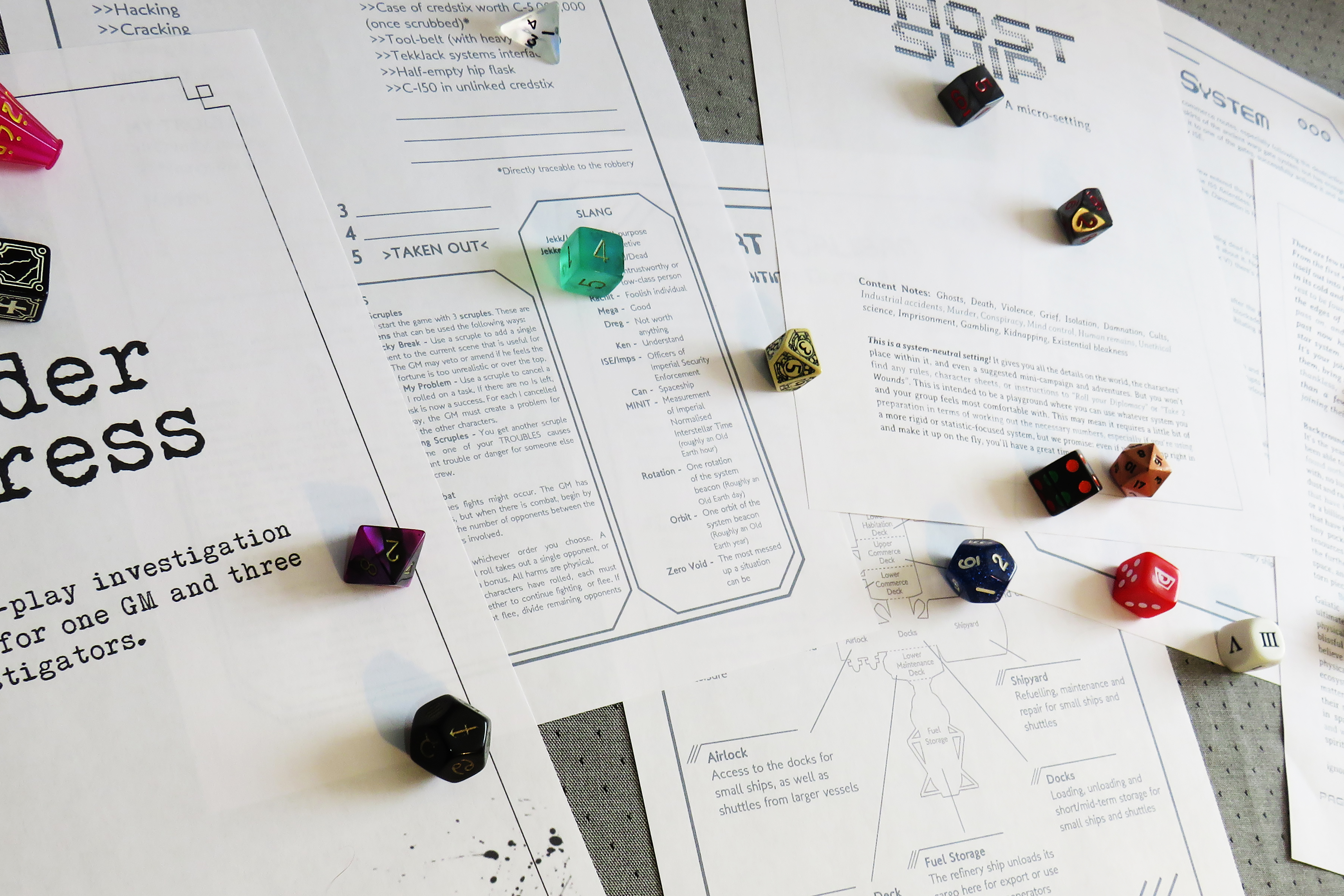 Multicoloured dice and printed game title sheets on a grey background.